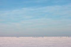 Einfacher und blauer Himmel des Schnees über einem Wintermeer Lizenzfreies Stockfoto