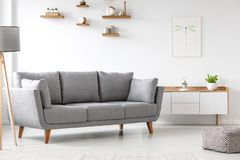 Einfaches, graues Sofa, das nahe bei einem weißen Schrank in Lebenro steht stockfotos