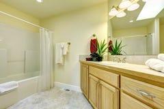 Einfaches großes Badezimmer mit Wanne- und Holzkabinetten. Lizenzfreie Stockfotos