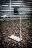Einfaches hölzernes Schwingen, das von den Seilen vor Blockhaus hängt Stockfotos