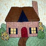 Einfaches Haus auf einer Steppdecke Stockbild