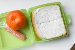 Einfaches Mittagessen im grünen Lunchbox, obenliegende Ansicht Stockfotografie