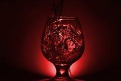 Einfaches Stilllebenfoto Whiskyglas-, Wasserstrahl- und schwachemrotes L lizenzfreies stockbild