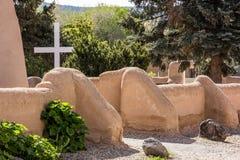 Einfaches weißes Kreuz hinter einer Kirchenwand des luftgetrockneten Ziegelsteines Lizenzfreies Stockfoto