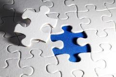 Einfaches weißes Puzzle, auf blauem Hintergrund Lizenzfreie Stockbilder