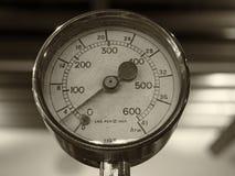 Einfarbiges Bild des Sepia eines alten glänzenden runden MessingManometers mit einer runden Skala markiert in den Zahlen lizenzfreies stockfoto