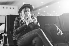 einfarbiges Bild Frauentourist im Hut, mit Rucksack sitzt am Flughafen und benutzt Smartphone Warteflache Landung des Mädchens Stockbilder