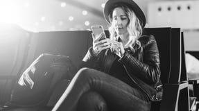 einfarbiges Bild Frauentourist im Hut, mit Rucksack sitzt am Flughafen und benutzt Smartphone Warteflache Landung des Mädchens Lizenzfreies Stockfoto