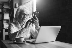 einfarbiges Bild Geschäftsfrau sitzt bei Tisch vor Laptop und benutzt Smartphone Ausbildung für Erwachsene Lizenzfreie Stockbilder