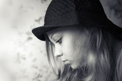Einfarbiges Nahaufnahmeprofilporträt des blonden Mädchens im schwarzen Hut stockfoto
