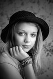 Einfarbiges Porträt der blonden Jugendlichen im schwarzen Hut lizenzfreie stockfotos