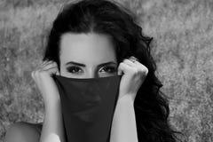Einfarbiges Porträt eines schönen Mädchens, das zur Kamera schaut Das Mädchen bedeckt ihr Gesicht mit einem Stoff Schwarzweiss-Fo stockfotografie