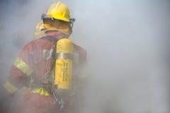 Einfassung des Feuerwehrmannes in Kraft mit Rauche Stockbild