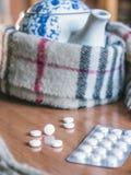 Einfassungen eines Schals zu einer Teekanne zusammen mit Kapseln lizenzfreies stockfoto