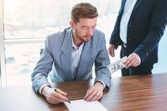 Einflussreicher Beamter, der seinem Kollegen ein Bestechungsgeld gibt stockfotos