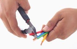 Einflussscherblock des Mannes Hand, zum des elektrischen Drahts zu entfernen Stockbild