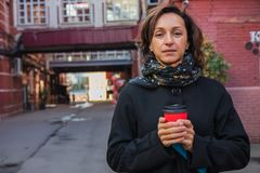 Einfrierende junge Dame im stilvollen schwarzen Mantel trinkt Kaffee lizenzfreies stockbild