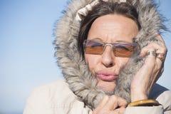 Einfrierende warme Winterjacke der Frau Stockfotografie
