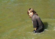 Einfrierender Junge, der im Wasser steht Stockbild