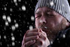 Einfrierender kalter Mann im Schneesturm Stockfoto