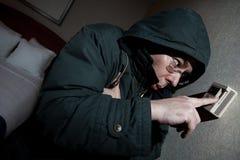 Einfrierender Mann, der Thermostat justiert Stockfoto