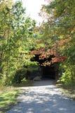 Eingang der überdachten Brücke versteckt durch Bäume Stockfotografie