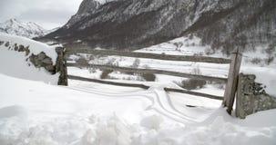 Eingang eines Bauernhofes in den Bergen bedeckt durch Schnee stock footage