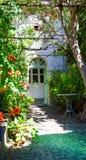Eingang eines Landhauses mit Blumen und Gartentisch Lizenzfreies Stockfoto