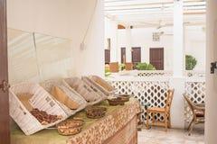 Eingang im schönen Restaurant in den sahnigen Farben mit Spezies auf Tabelle nahe Stühlen Lizenzfreie Stockbilder