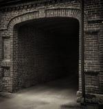 Eingangstunnel des alten Ziegelsteines. Dunkler Bogen. Schwarzes Weiß. Stockfotografie