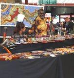 Eingeborener Mann verkauft eingeborene Kunst an der Königin Victoria Market, Melbourne, Australien Stockbilder