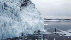 Eingefroren nach Winterstürmen, spritzt Wasser auf den Klippen des Ufers Der Baikalsee im Vorfrühling sibirien Russland stock video