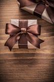 Eingepackte Geschenkbehälter mit braunen Bändern auf hölzernem Brett der Weinlese Stockbild