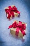 Eingepackte goldene Geschenke mit rotem Bogen auf verkratztem metallischem Hintergrund Stockfotos