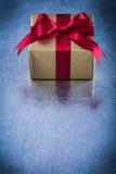 Eingepacktes anwesendes mit rotem Band auf metallischem Hintergrundfeiertagsbetrug Lizenzfreie Stockfotos