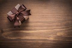 Eingepacktes Geschenk Versionsfeiertagen des hölzernen Brettes der Weinlese an den horizontalen legen herein Stockbilder