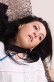 Eingeschnürte Krankenschwester auf dem Sofa (nachgemacht) Lizenzfreie Stockfotografie