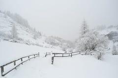 Eingeschneites Feld und Bretterzaun im alpinen Dorf stockbilder