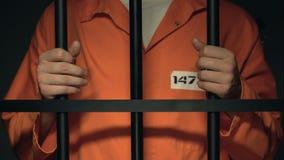 Eingesperrte männliche Stellung hinter den Gefängnisstangen, sie halten, alleine Gefangenschaft stock video footage