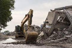 Eingestürztes Industriegebäude mit einem enormen Schaufelbagger Stockbild