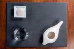 Eingestellt f?r nasale Reinigung mit neti Topf, ayurvedic Medizinsystem auf einem schwarzen Schiefer lizenzfreie stockfotos