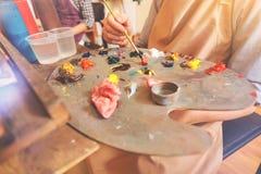 Eingestuft herauf Ansicht über den Künstler, der helle Farben auf Palette mischt lizenzfreies stockbild