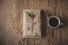 Eingewickelte Bücher auf einer Tabelle und Weihnachtslichtern Stockfoto