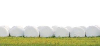 Eingewickelte Staplungssilageballen rudern, lokalisiert ringsum weiße Plastikfilmheurollen, Heulagenstapel-Reihenpanorama, horizo stockfoto