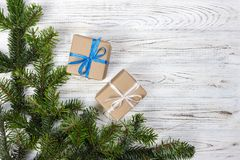 Eingewickelte Weihnachtsgeschenke auf dunklem rustikalem Holztisch mit Kiefernkegeln und -Tannenzweigen Mit Kopienraum für Ihren  Stockfotos
