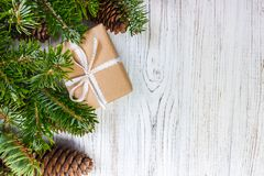 Eingewickelte Weihnachtsgeschenke auf dunklem rustikalem Holztisch mit Kiefernkegeln und -Tannenzweigen Mit Kopienraum für Ihren  Lizenzfreie Stockfotos
