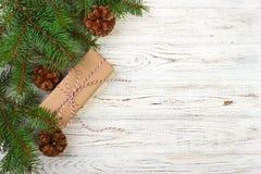 Eingewickelte Weihnachtsgeschenke auf dunklem rustikalem Holztisch mit Kiefernkegeln und -Tannenzweigen Mit Kopienraum für Ihren  Stockfoto