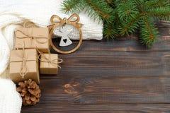 Eingewickelte Weihnachtsgeschenke mit weißem Engel auf dunklem rustikalem Holztisch mit Kiefernkegeln und -Tannenzweigen Mit Kopi Stockfoto