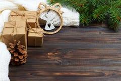 Eingewickelte Weihnachtsgeschenke mit weißem Engel auf dunklem rustikalem Holztisch mit Kiefernkegeln und -Tannenzweigen Mit Kopi Lizenzfreies Stockfoto