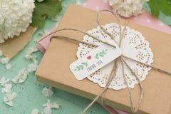 Eingewickeltes Geschenk und Blumen Stockfoto